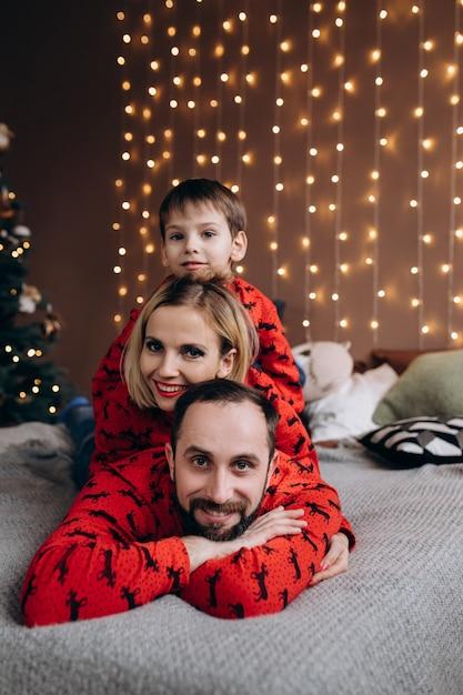 Aantrekkelijke ouders en hun zoontje in rode truien hebben plezier voor het rusten op het bed voor een kerst Gratis Foto