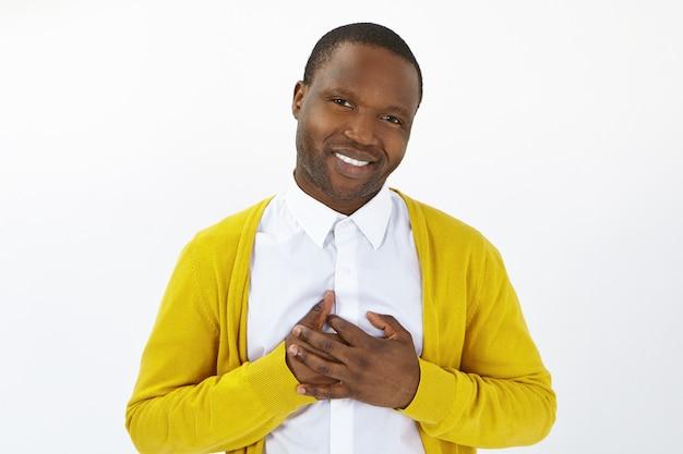 Aantrekkelijke positieve jonge afro man camera kijken met open waarderende glimlach, handen op zijn borst houden, dankbaarheid tonen, dankbaar voelen voor hulp. menselijke emoties, reacties en gevoelens Gratis Foto