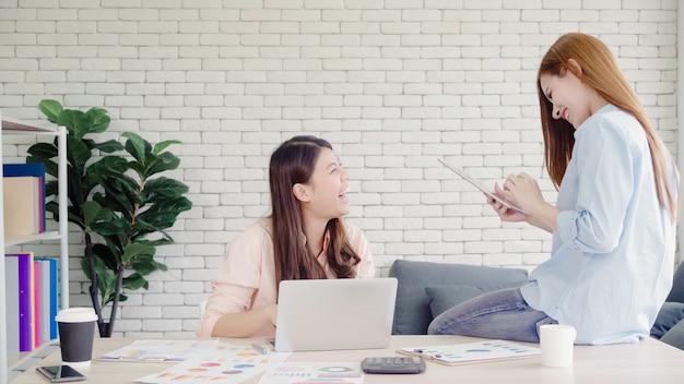 Aantrekkelijke slimme creatieve aziatische bedrijfsvrouwen in slimme vrijetijdskleding die aan laptop terwijl het zitten werken Gratis Foto