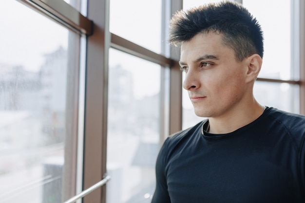 Aantrekkelijke sportieve man bij het raam. atleet poseren in de buurt van ruime ramen. sportschool en sport. Gratis Foto