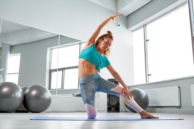Aantrekkelijke sportvrouw die oefeningen op de vloer in de moderne pilatesstudio doen. mooi sportief meisje lenig-up en strekt haar benen en armen Premium Foto