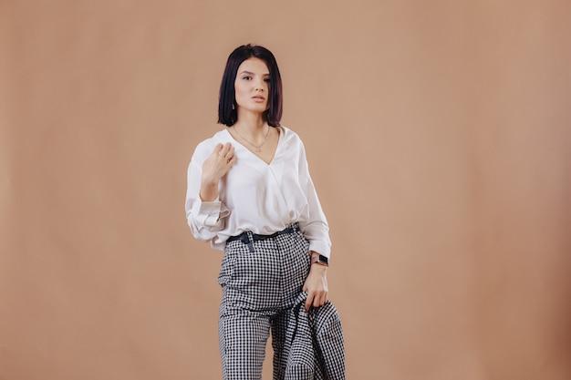 Aantrekkelijke stijlvolle jong meisje in zakelijke kleding die zich voordeed op crème achtergrond. concept van stijlvolle kleding en verfijning. Gratis Foto