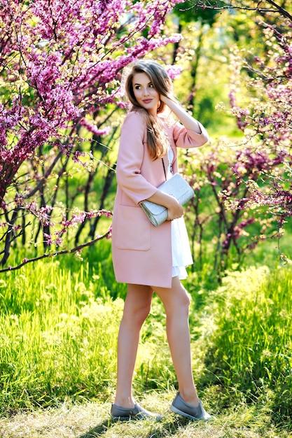 Aantrekkelijke stijlvolle jonge vrouw in lichte witte jurk, roze jas, met lang haar wandelen in de tuin met bloeiende sakura Gratis Foto