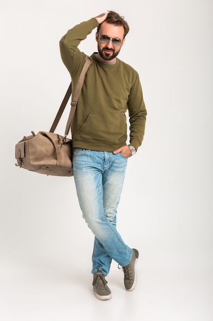 Aantrekkelijke stijlvolle man reiziger geïsoleerd staande met tas knap gekleed in spijkerbroek en sweatshot Gratis Foto