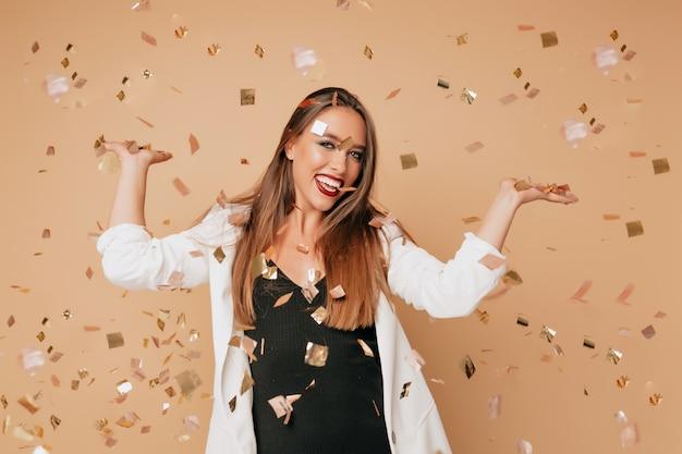 Aantrekkelijke stijlvolle mooie vrouw met lichtbruin haar en lichte make-up dragen zwarte jurk en witte jas poseren op beige muur met confetti, ware gelukkige emoties, vakantie, feest, verjaardag Gratis Foto