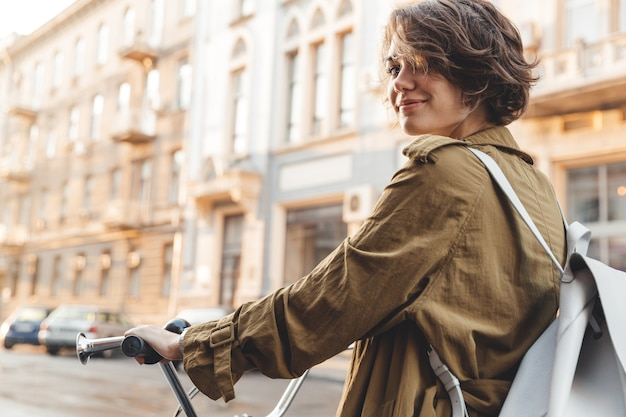 Aantrekkelijke stijlvolle vrouw dragen jas fietsen op een stad straat Premium Foto