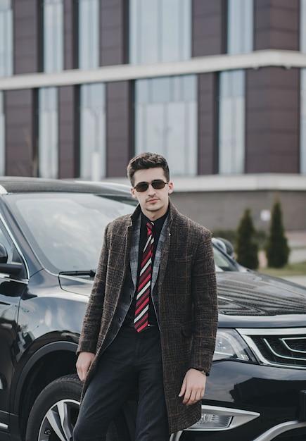 Aantrekkelijke succesvolle jonge zakenman in een pak in de buurt van zijn auto Premium Foto