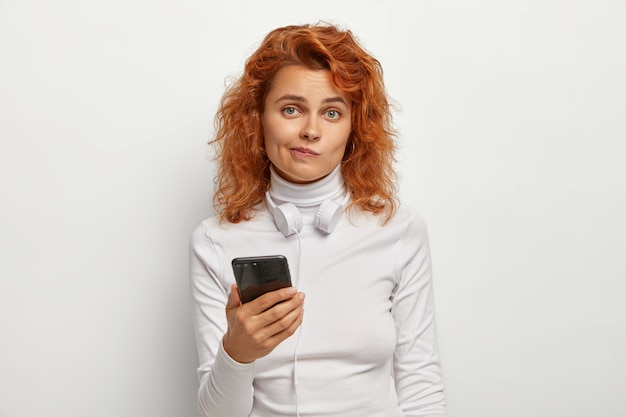 Aantrekkelijke verwarde roodharige meloman luistert naar muziek via een koptelefoon die is aangesloten op een smartphone, downloadt liedjes naar de afspeellijst, drukt lippen op elkaar, ziet er verwarrend uit, draagt witte kleren. technologie, levensstijl Gratis Foto