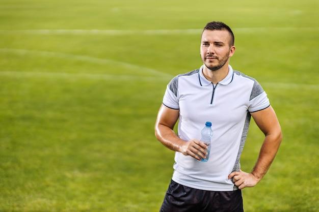 Aantrekkelijke voetballer in vorm staande op het veld en fles water te houden. Premium Foto