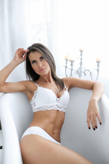 Aantrekkelijke volwassen vrouw in erotische witte lingerie in de badkuip Gratis Foto