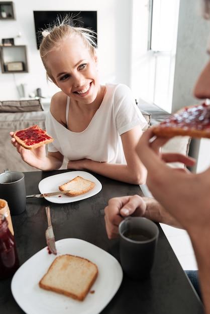 Aantrekkelijke vrolijke vrouw die haar man bekijkt terwijl zij die ontbijt eten Gratis Foto