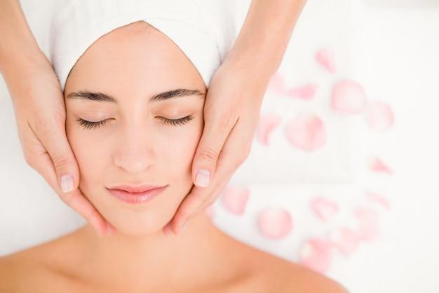 Aantrekkelijke vrouw die gezichtsmassage ontvangt op kuuroordcentrum Premium Foto
