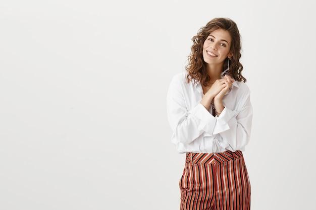 Aantrekkelijke vrouw die ontroerd kijkt, blij om een compliment te ontvangen Gratis Foto