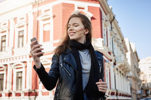 Aantrekkelijke vrouw die rond stad loopt, die smartphone houdt Gratis Foto