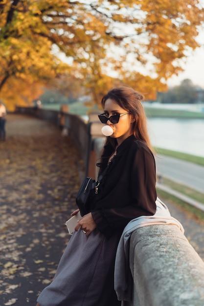 Aantrekkelijke vrouw die smartphone in openlucht in het park gebruiken Gratis Foto
