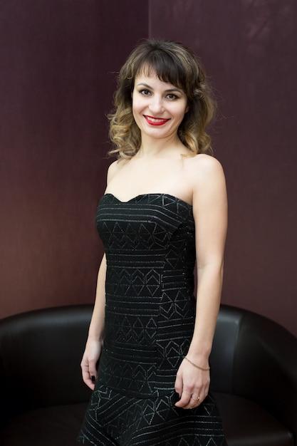 Aantrekkelijke vrouw die zich voordeed op zwarte jurk Premium Foto