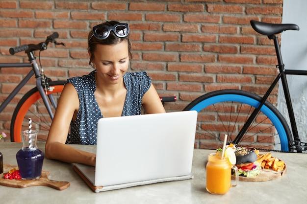 Aantrekkelijke vrouw die zonnebril op haar hoofd draagt dat online winkelt, gebruikend snelle internetverbinding, zittend voor open laptop computer tijdens lunch Gratis Foto
