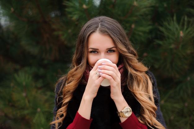 Aantrekkelijke vrouw heeft een koffiepauze op straat in herfstdag. Premium Foto