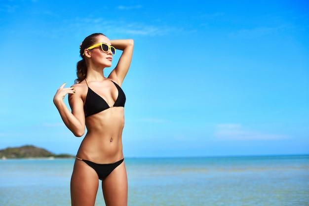 Aantrekkelijke vrouw in bikini genieten van een zonnige dag Gratis Foto