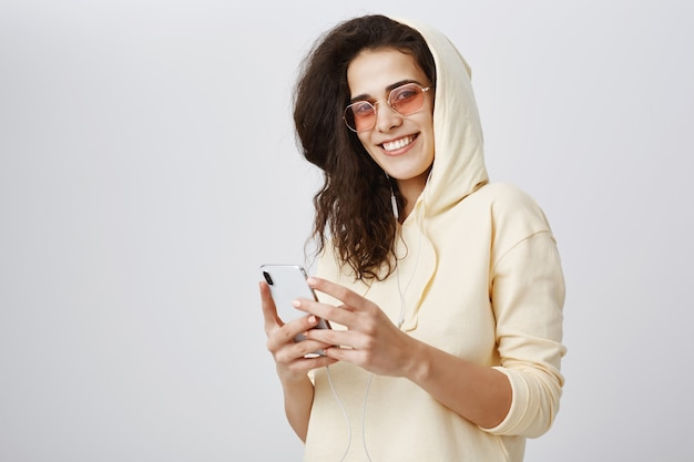 Aantrekkelijke vrouw in zonnebril met behulp van smartphone en glimlachen Gratis Foto