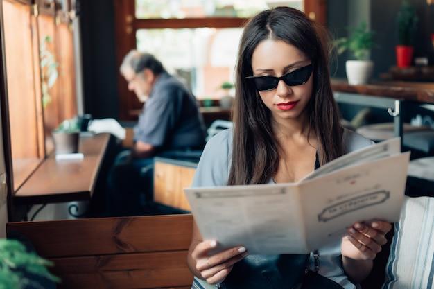 Aantrekkelijke vrouw in zonnebril zit in een restaurant. Gratis Foto