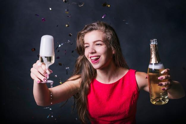 Aantrekkelijke vrouw met druipende glas champagne op feestje Gratis Foto