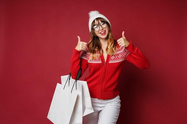 Aantrekkelijke vrouw met golvende haren staan met witte boodschappentassen Gratis Foto