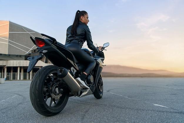 Aantrekkelijke vrouw met lang haar in zwarte leren jas en broek op buiten parkeren met stijlvolle sportmotorfiets bij zonsondergang. Premium Foto