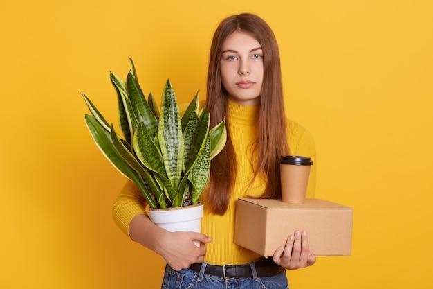 Aantrekkelijke vrouw met lang mooi haar, gekleed in casual kleding, boos vrouw pikt haar spullen van kantoor na ontslag, poseren tegen gele muur. Gratis Foto
