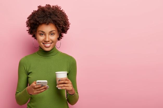 Aantrekkelijke vrouw met tevreden gezichtsuitdrukking, houdt mobiele telefoon en koffie om mee te nemen, gekleed in groene kleding, stuurt sms, communiceert online in chat, geïsoleerd over roze muur Gratis Foto