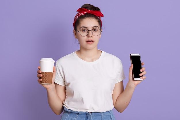 Aantrekkelijke vrouw met verbaasde gezichtsuitdrukking, houdt mobiele telefoon met leeg scherm en koffie te gaan Gratis Foto