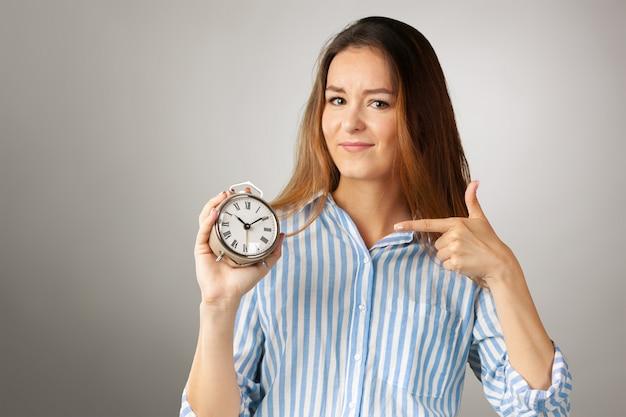 Aantrekkelijke vrouw met wekker. bedrijfsconcept tijd management Premium Foto