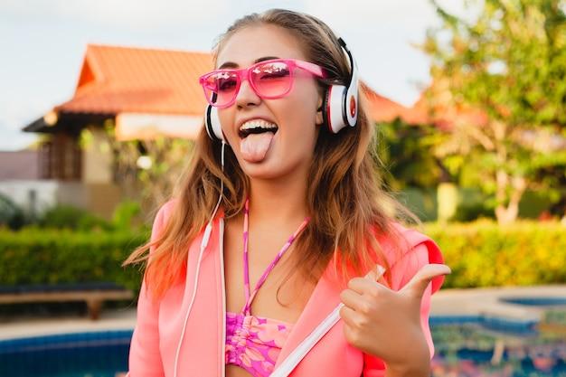 Aantrekkelijke vrouw sporten bij zwembad in kleurrijke roze hoodie dragen van een zonnebril luisteren naar muziek in koptelefoon op zomervakantie, tennissen, sport stijl, grappig gezicht duim omhoog Gratis Foto