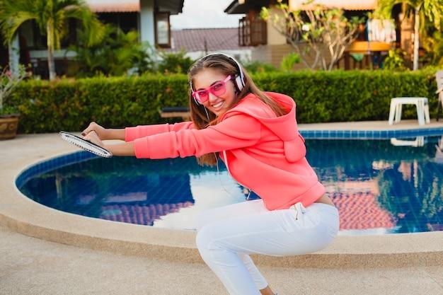 Aantrekkelijke vrouw sporten bij zwembad in kleurrijke roze hoodie dragen van een zonnebril luisteren naar muziek in koptelefoon op zomervakantie, tennissen, sport stijl Gratis Foto