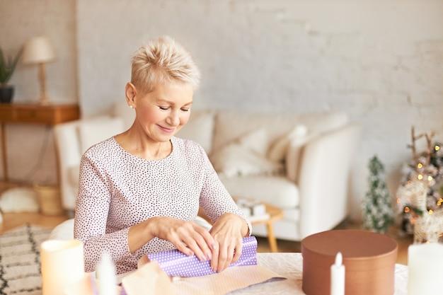 Aantrekkelijke vrouw van middelbare leeftijd met blonde korte kapsel zittend aan tafel in de woonkamer, kerstcadeau voor man verpakken in cadeau papier Gratis Foto