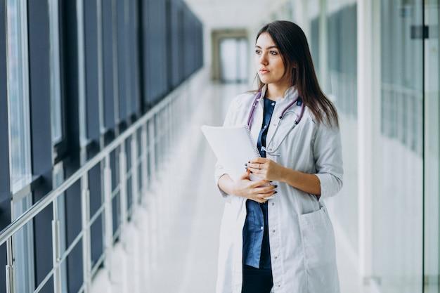 Aantrekkelijke vrouwelijke arts die zich met documenten bij het ziekenhuis bevindt Gratis Foto