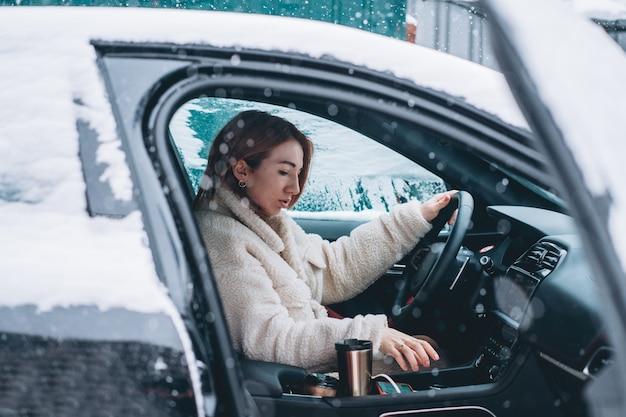 Aantrekkelijke vrouwenbestuurder nsitting achter het stuur in haar auto Gratis Foto