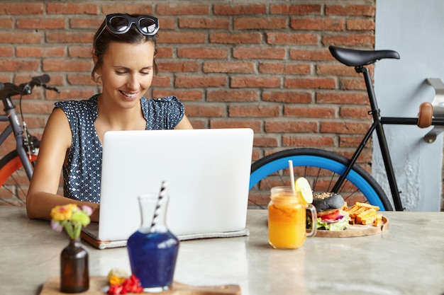 Aantrekkelijke vrouwenfotograaf die beelden retoucheert die fotobewerker met behulp van, lunchend, voor generische laptop zitten. studentenmeisje die online op notitieboekje bestuderen Gratis Foto