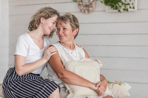 Aantrekkelijke vrouwenzitting met haar moeder op bank die elkaar bekijken Gratis Foto