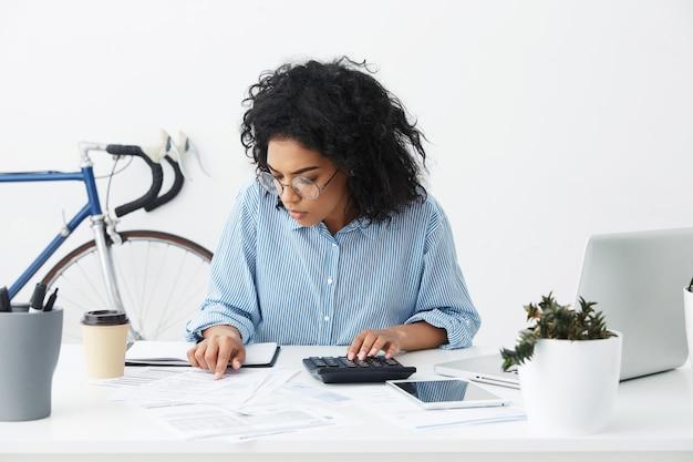 Aantrekkelijke zekere jonge onderneemster met krullend kapsel die calculator gebruiken Gratis Foto