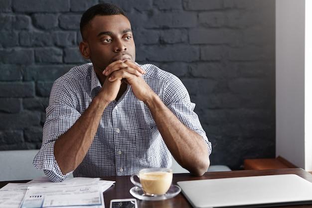 Aantrekkelijke zelfverzekerde jonge afro-amerikaanse mannelijke ondernemer met een doordachte en gerichte blik Gratis Foto