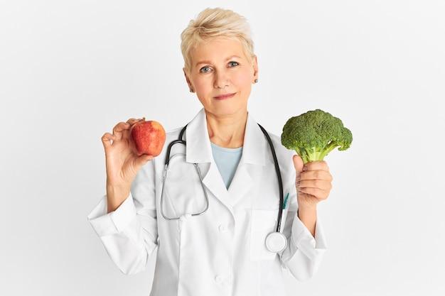 Aantrekkelijke zelfverzekerde volwassen blanke vrouwelijke arts die rode appel en groene broccoli houdt als onderdeel van een gezond dieet om het risico op sommige chronische ziekten te verminderen. voedsel, voeding en gezondheidsconcept Gratis Foto
