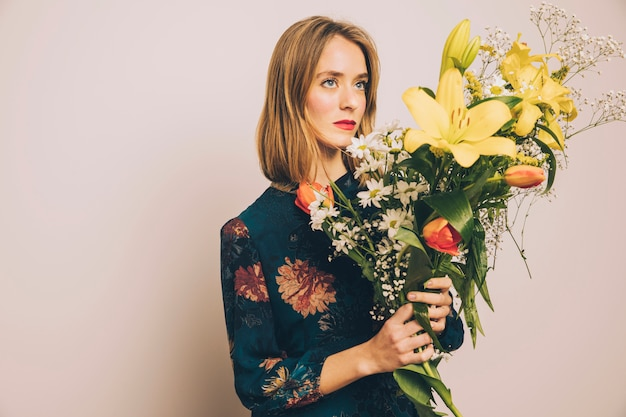 Aantrekkelijke zelfverzekerde vrouw met groot boeket bloemen Gratis Foto