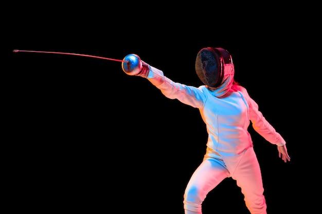 Aanvallen. tienermeisje in hekwerkkostuum met in hand zwaard geïsoleerd op zwarte muur, neonlicht. jong model oefenen en trainen in beweging, actie. copyspace. sport, jeugd, gezonde levensstijl. Gratis Foto