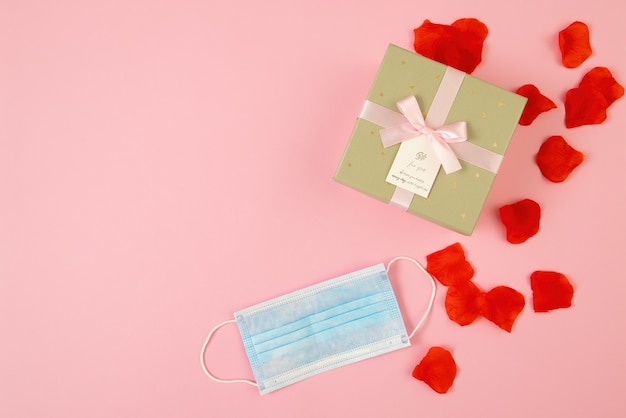 Aanwezig op roze achtergrond met blauw chirurgisch gezichtsmasker in plat lag samenstelling Premium Foto