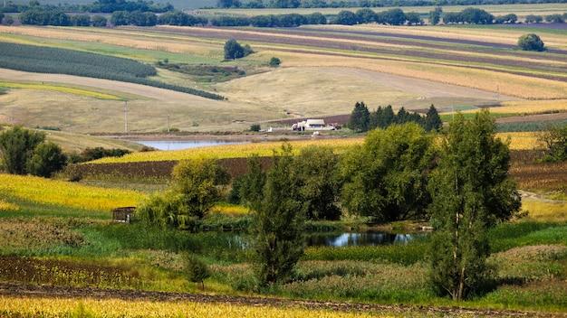 Aard van moldavië, dal met twee meren, weelderige bomen, ingezaaide velden en een huis aan het water Gratis Foto