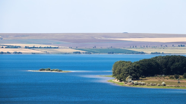 Aard van moldavië, meer met eilandje, weide met weelderige bomen aan de rechterkant, brede velden zichtbaar in de verte Gratis Foto