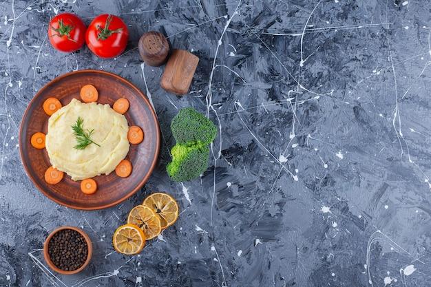 Aardappelpuree en gesneden wortelen op een bord naast groenten en kruidenkommen, op de blauwe tafel. Gratis Foto