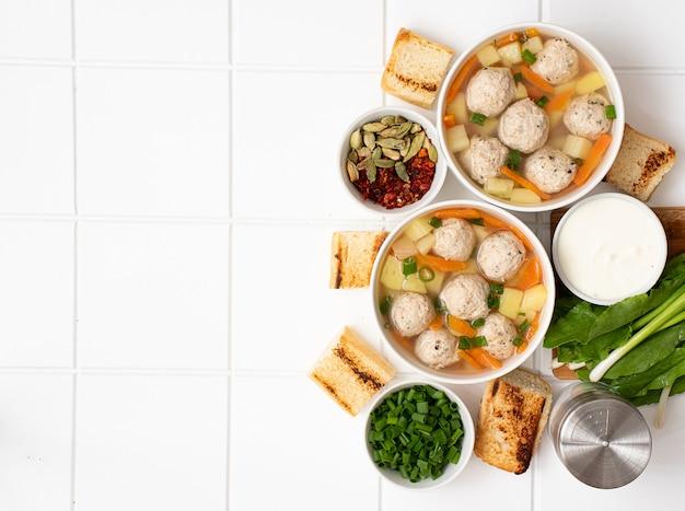 Aardappelsoep met gehaktballetjes, worteltjes en kruiden Premium Foto