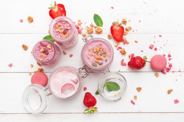 Aardbei met yoghurt op witte rustieke houten achtergrond. roomdessert Premium Foto